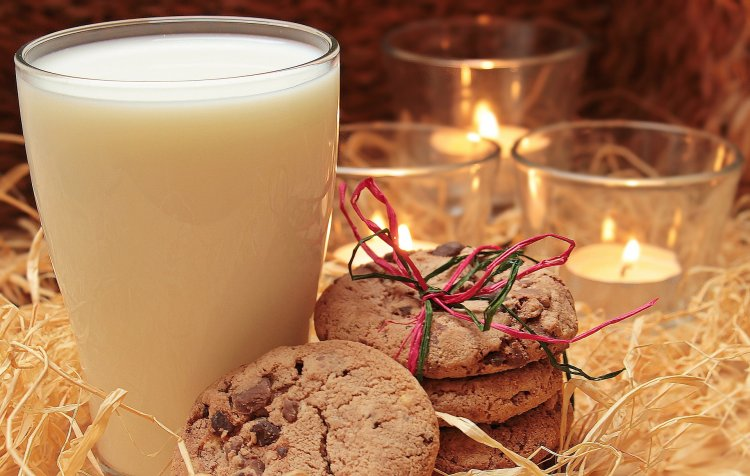 Glass of milk with cookies & candles